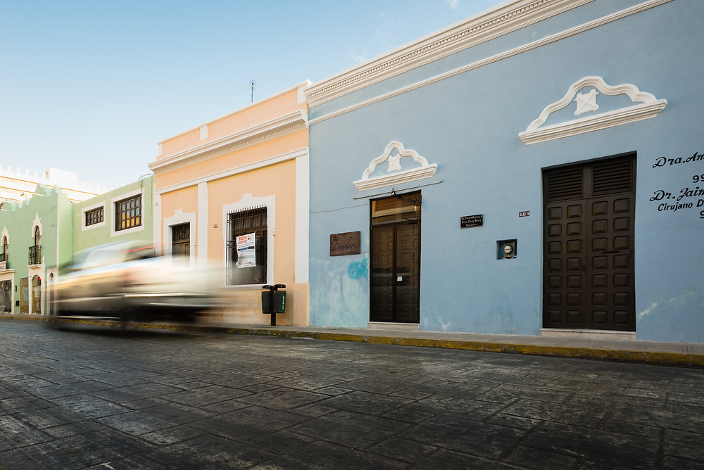 Car speeding past Colonial architecure in Merida, Mexico