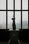 silhouette of classic sculpture display against a clear stained glass window