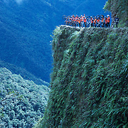 "Mountain Biking on Death Road, Bolivia...A tour group of Mountain Bikers pose for a photograph on a landmark bend of the infamous narrow dirt road, most of the road no wider than 3.2 meter's, is cut into the side of the mountain with sheer drops to the left of up to 600 meter's with virtually no safety rails on the winding steep decent...The North Yugas Road is a 64 Kilometer road leading from La Paz to Corioico. It is legendary for it's extreme danger and in 1995 the Inter American Development Bank christened is as the ""world's most dangerous road"".. The road was built in the 1930's during the Chaco War by Paraguayan prisoners to connect the Amazon rainforest region of Northern Bolivia to it's capital City La Paz. One estimate is that 200 to 300 travelers were killed yearly along the road. On 24 July 1983, a bus veered off the Yungas Road and into a canyon, killing more than 100 passengers in what is said to be Bolivia's worst road accident..A new stretch of the La Paz-Coroico highroad was opened in 2006 to bypass the notorious stretch known as death road..The danger of the road has now made it a popular tourist destination starting in the 1990's and drawing thrill-seekers and mountain bike enthusiasts who ride on the 64km mainly downhill stretch from La Cumbre, a 4,700 meter peak to Yolosa, a decent of 3600 meter's (11,800 feet). The journey includes breathtaking views of snow covered peaks and towering cliffs and starts along modern asphalted road before entering the jungle itself and the most dangerous and notorious part of the ride. The infamous narrow dirt road, most of the road no wider than 3.2 meter's, is cut into the side of the mountain with sheer drops to the left of up to 600 meter's with virtually no safety rails on the winding steep decent..There are now many tour operators catering to this activity, providing information, guides, transport and equipment. Nevertheless, the Yungas Road remains dangerous. At least 13 of these cyclists died on the ride s"