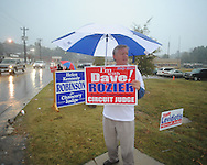 Mickey Watkins holds a campaign sign as voters go to the polls in the rain at the National Guard Armory in Oxford, Miss. on Tuesday, November 2, 2010.