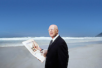 Senior business man holding newspaper standing on beach portrait