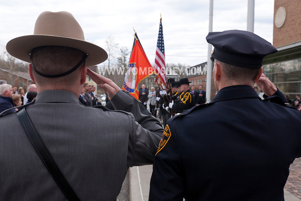 Goshen, New York - Police officers salute at the start of the Orange County Law Enforcement Officer Memorial Service in front of the county courthouse on May 2, 2014. The memorial service honors the memory of the 27 members of the Orange County law enforcement community that died in the line of duty. The service also pays tribute the families and loved ones left behind for their courage, dignity and perseverance.