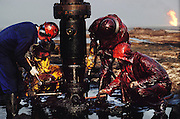 The Red Adair Company capping an oil well after they extinguished the fire. The burning Al Burgan oil fields in Kuwait after the end of the Gulf War in May of 1991 were covered in oil that rained down from the clouds of oil smoke and oil shooting into the air after a fire had been extinguished. More than 700 wells were set ablaze by retreating Iraqi troops creating the largest man-made environmental disaster in history.