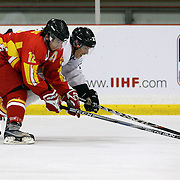 Li Ning, China, and James Currey, New Zealand, challenge for the puck during the China V New Zealand match during the 2012 IIHF Ice Hockey World Championships Division 3 held at Dunedin Ice Stadium. Dunedin, Otago, New Zealand. 21st January 2012. Photo Tim Clayton