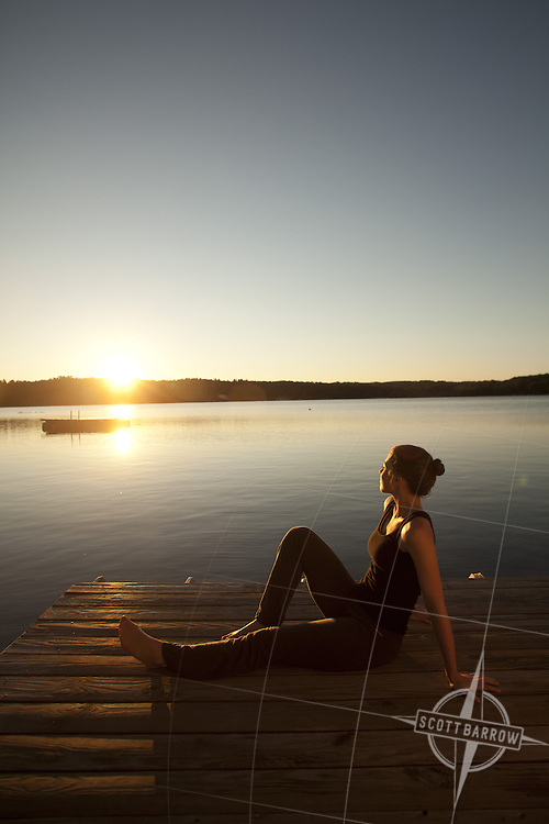 A woman sitting lakeside enjoying the sunrise.