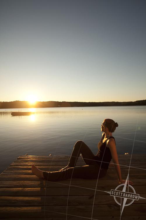 A woman sitting lakeside enjoying the sunrise.