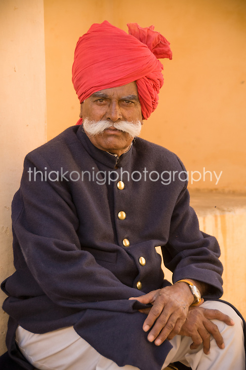 Portrait of a man with a red turban and a wide, white mustache, wearing a blue coat with brass buttons, Jaipur, India