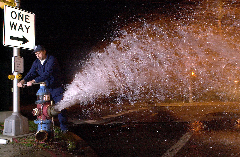 Wild Art.photo by Brian Leddy    3-30-00.mac1/news/metro.Mark Rosheck turns the water off on a fire hydrant on the corner of Marion and Portage streets. The South Bend Water Works was emptying some of the city's fire hydrants Thursday night.