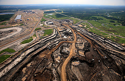 CANADA ALBERTA FORT MCMURRAY 20JUL09 - Aerial view of CNRL (Canadian National Resrouces Limited) tarsands mining operations in the Boreal forest north of Fort McMurray, northern Alberta, Canada...The tar sand deposits lie under 141,000 square kilometres of sparsely populated boreal forest and muskeg and contain about 1.7 trillion barrels of bitumen in-place, comparable in magnitude to the world's total proven reserves of conventional petroleum. Current projections state that production will  grow from 1.2 million barrels per day (190,000 m³/d) in 2008 to 3.3 million barrels per day (520,000 m³/d) in 2020 which would place Canada among the four or five largest oil-producing countries in the world...The industry has brought wealth and an economic boom to the region but also created an environmental disaster downstream from the Athabasca river, polluting the lakes where water and fish are contaminated. The native Indian tribes of the Mikisew, Cree, Dene and other smaller First Nations are seeing their natural habitat destroyed and are largely powerless to stop or slow down the rapid expansion of the oil sands development, Canada's number one economic driver...jre/Photo by Jiri Rezac / GREENPEACE..© Jiri Rezac 2009