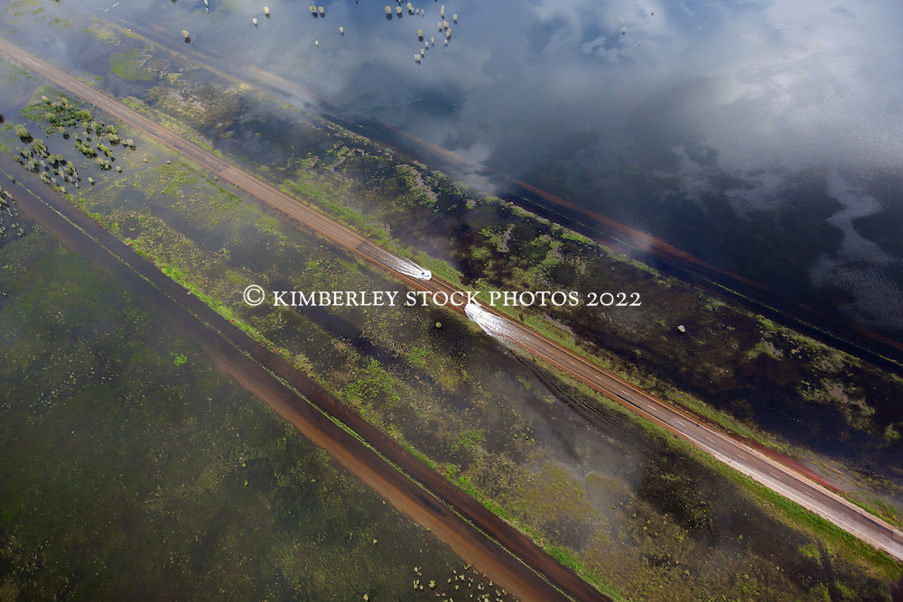 Two vehicles approach each other on a wet road on Roebuck Plains in the Kimberley wet season.  A sustained wet season brought flooding on Roebuck Plains, with water over the main highway.