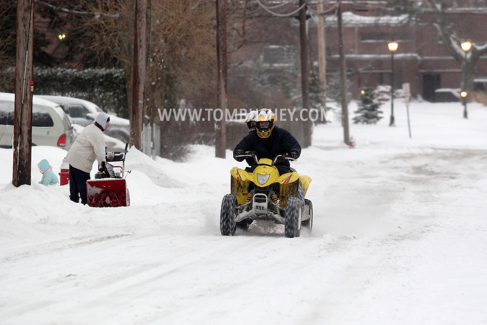 Middletown, N.Y. - Two teenagers ride an ATV down the street after a snowstorm on Feb. 14, 2007.