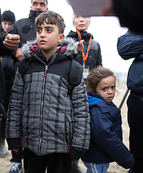 © Licensed to London News Pictures . 24/10/2016 . Calais , France . A Kurdish boy and girl , reportedly ten and four years old respectively , leaving the Jungle migrant camp in Calais , Northern France , with their parents , on the day of a planned eviction and start of the destruction of the camp . Photo credit: Joel Goodman/LNP