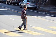 Een oudere man steekt de straat over in Japan Town in San Francisco. De Amerikaanse stad San Francisco aan de westkust is een van de grootste steden in Amerika en kenmerkt zich door de steile heuvels in de stad.<br /> <br /> An elderly man crosses the road in Japan Town in San Francisco. The US city of San Francisco on the west coast is one of the largest cities in America and is characterized by the steep hills in the city.