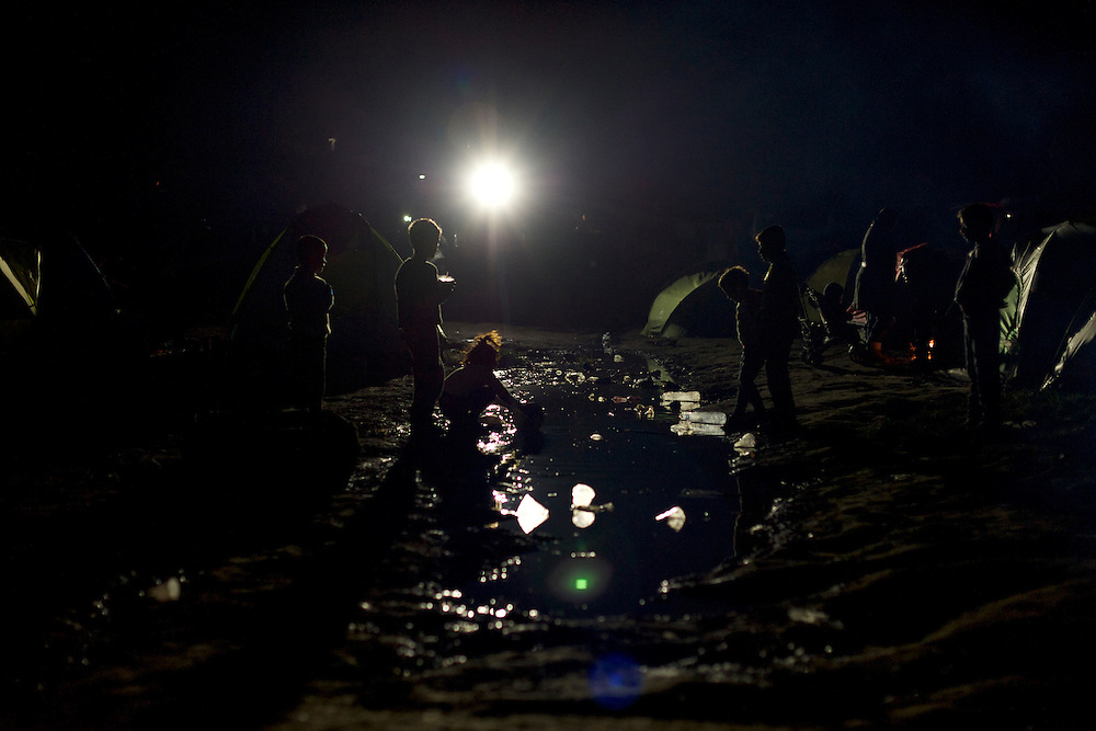 Migrant children play in dirty water surrounding tents at the Greek-Macedonian border station of Idomeni, Greece. Around 13,000 migrants and refugees, mostly from the Middle East and African nations, are believe to be stranded here awaiting a chance to proceed their journey towards Germany and other northern European countries.