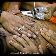 Devotees help as another is given a tattoos during festivities at the Wat Bang Phra tattoo festival in Nakhon Chai Si province on the outskirts of Bangkok, Thailand.