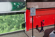 A pedestrian lights a cigarette while walking beneath a sporting-themed hoarding of green and red, on 31st August 2017, in Brixton, London England.