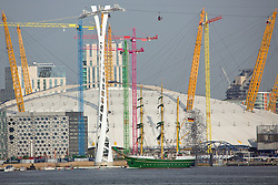 © Licensed to London News Pictures. 15/05/2016. Alexander von Humboldt II passing the O2 and the colourblocking cranes designed by artist Morag Myerscough. Stunning German sail training ship Alexander Von Humboldt II makes her way down the Thames after a weekend in London. The distinctive ship is known for her green hull, yellow masts and green sails. The 65-metre long ship was launched in 2011 as a successor to an earlier tall ship of the same name and cost €15 million to build. Credit: Rob Powell/LNP