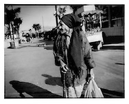 Impoverished aged woman in tattered clothes slowly makes her way along Tijuana street, Baja California, Mexico.   Lack of water is a major factor contributing to pervasive poverty south of the border.