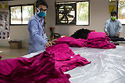 A man checks the quality of C & A T-shirts on a production line of Pratibha Syntax factory, where organic cotton is being used to make clothes.
