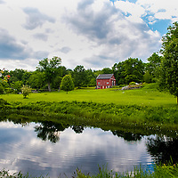 Eastern Connecticut. Green grass,old farm house, barn and pond.