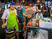 24 MARCH 2017 - BANGKOK, THAILAND: A street food vendor makes an omelette for a customer on Sukhumvit Soi 55 (Thong Lo). His cart is in an area where city officials have announced they will evict the food vendors from. Food cart vendors along Sukhumvit Road between Sois 55 (Thong Lo) and 69 (Phra Khanong) in Bangkok have been told by city officials that they have to leave the area by 17 April. It's a part of an effort by Bangkok city government, supported by the ruling junta, to take back the city's sidewalks. The evictions in the area are the latest in mass evictions of Bangkok street food vendors after similar actions elsewhere on Sukhumvit, in the Ari area, in Silom/Patpong and Ratchaprasong neighborhoods. The vendors in Thong Lo/Phra Khanong are popular with local office workers because most of the formal restaurants in the area serve foreign tourists and upper class Thais and are very expensive. The street food carts serve meals starting at about 35Baht ($1US). The city has not announced if they will provide alternative locations for the carts.     PHOTO BY JACK KURTZ