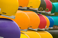 colorful white water canoes on their rakes waiting for canoeist