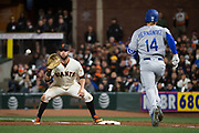 San Francisco Giants first baseman Brandon Belt (9) makes a catch at first base on a hit by Los Angeles Dodgers shortstop Enrique Hernandez (14) at AT&T Park in San Francisco, California, on April 24, 2017. (Stan Olszewski/Special to S.F. Examiner)