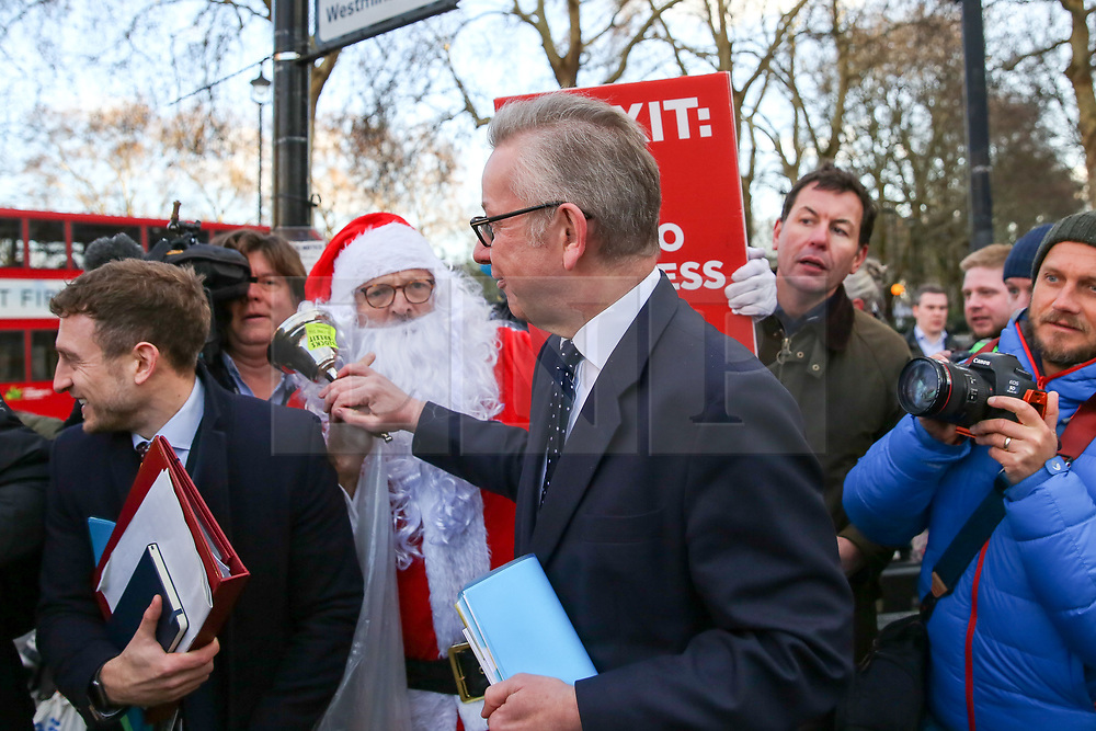 © Licensed to London News Pictures. 12/12/2018. London, UK. Michael Gove - Secretary of State for Environment, Food and Rural Affairs is hassled by the a Brexit protester dressed in Santa Claus as he leaves the media centre in College Green. The British Prime Minister Theresa May announced that she will contest tonight's vote of no confidence in her leadership. Photo credit: Dinendra Haria/LNP