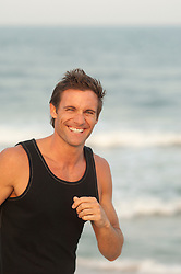 good looking man at the beach in a tank top laughing and smiling