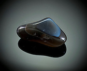 Cutout of a banded agate gemstone on black background