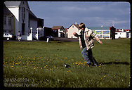 Boy chases puffin chick in Heimaey park to rescue the flightless fledgling and release at shore. Iceland