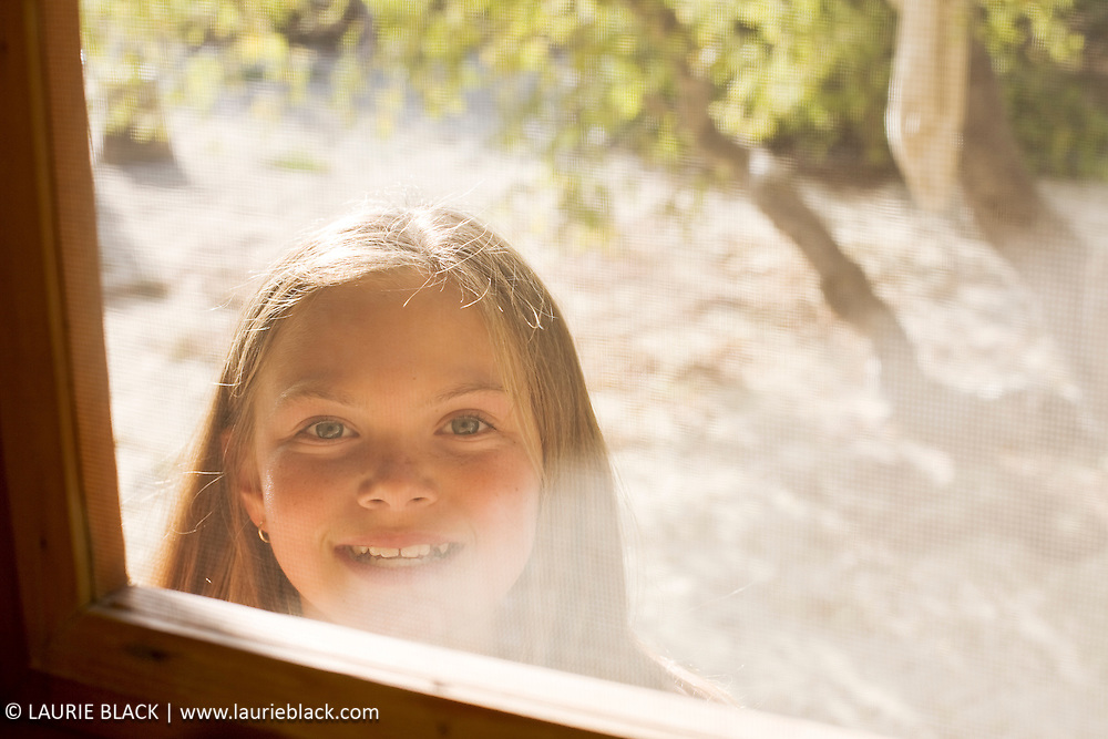 Happy young girl knocking at door.