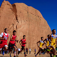 Racers dash off the starting line in the boys varsity race of the Gallup Invitational Saturday at Red Rock Park in Gallup.