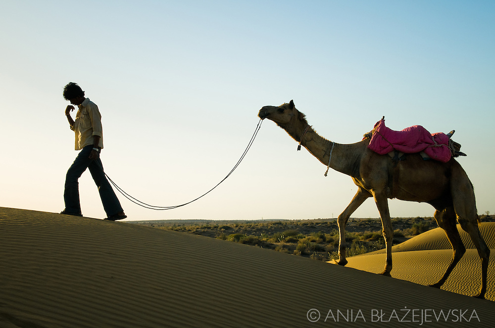 India, Jaisalmer. A boy with his camel on Thar Desert in Rajasthan.
