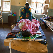 Women lie two to a bed at the Geita district hospital. Geita, the heart of the lucrative gold mining industry in Tanzania, remains a largely impoverished area with poor quality facilities, like the local hospital.