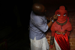 April 30, 2019 - Lalitpur, Nepal - A priest giving touches on an idol of the God of Rain ''Rato Machhindranath'' for the deity chariot procession inside the divine being's temple in Lalitpur, Nepal on Tuesday, April 30, 2019. Both Hindus and Buddhists worship Rato Machhindranath the God of Rain praying for good harvest. Devotees worship Machhendranath to prevent drought during the rice harvest season. A chariot of the deity placed inside is paraded around the ancient city and thousands of devotees from across the valley come to worship the God of Rain. (Credit Image: © Skanda Gautam/ZUMA Wire)