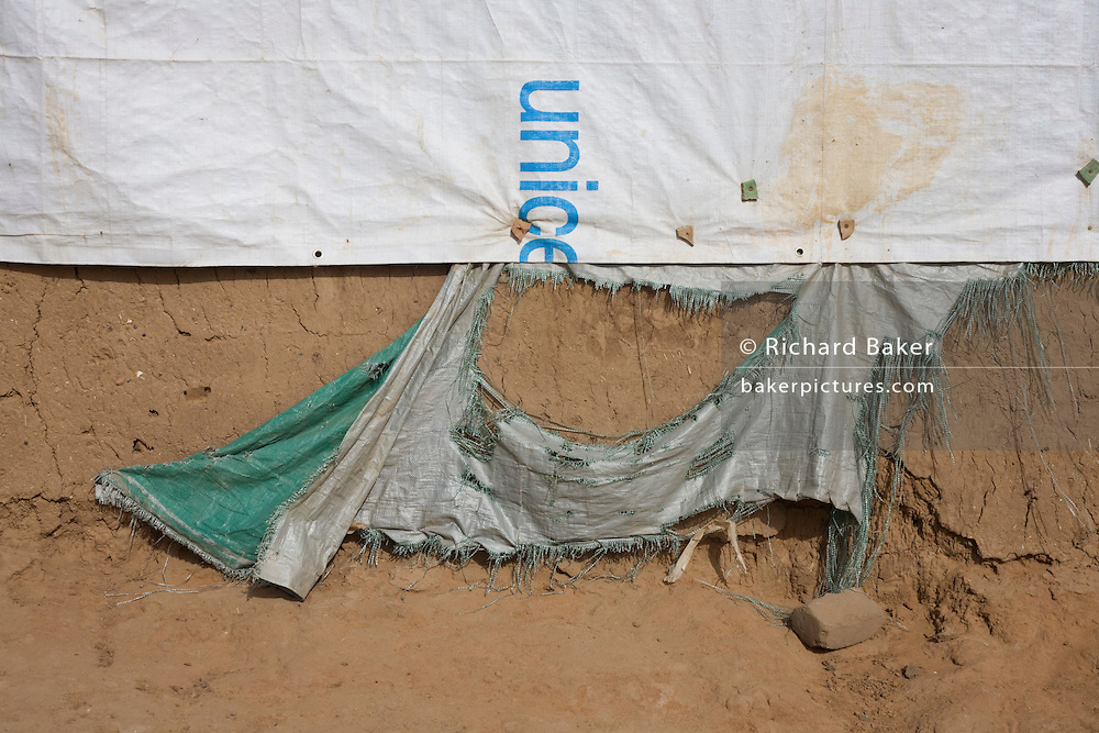 Torn UNICEF sheeting used to cover a makeshift roof lining of a home in the 4 sq km Abu Shouk refugee camp which is (disputedly) home to 38,000 displaced persons and families on the outskirts of the front-line town of Al Fasher (also spelled, Al-Fashir) in north Darfur. .