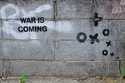 "Street art ""war is coming"" stencilled by prominent artist  XooooX on wall in Berlin Germany"