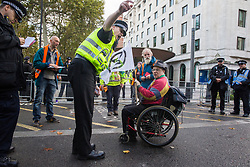 London, UK. 13 October, 2019. A police officer serves a notice under Section 14 of the Public Order Act 1986 to a disabled climate activist from Extinction Rebellion during a protest outside New Scotland Yard against tactics employed by police officers which impinge on the right to protest of disabled activists, including the confiscation of wheelchairs, wheelchair ramps, accessible toilets and tents.