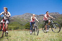 Two teenage boys and girl (16-17 years) biking mountains in background