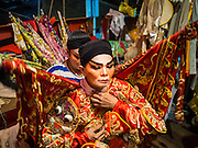18 JANUARY 2015 - BANGKOK, THAILAND:  A performer with the Sai Yong Hong Opera Troupe puts on her costume before a performance at the Chaomae Thapthim Shrine, a Chinese shrine in a working class neighborhood of Bangkok near the Chulalongkorn University campus. The troupe's nine night performance at the shrine is an annual tradition and is the start of the Lunar New Year celebrations in the neighborhood. The performance is the shrine's way of thanking the Gods for making the year that is ending a successful one. Lunar New Year, also called Chinese New Year, is officially February 19 this year. Teochew opera is a form of Chinese opera that is popular in Thailand and Malaysia.             PHOTO BY JACK KURTZ