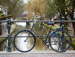 Detail of parked bicycle on bridge in Utrecht beside Oude Gracht or Old Canal in The Netherlands