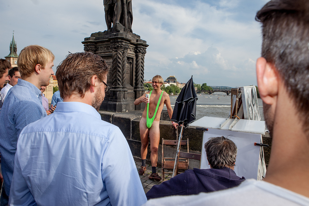 "A German tourist getting painted in a ""Borat"" like swimming dress on Charles Bridge in Prague. The Charles Bridge (Czech: Karlův most) is a famous historic bridge that crosses the Vltava river in Prague, Czech Republic and is probably the Nr.1 tourists magnet in the city."