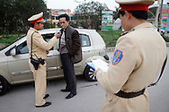A driver is tested with breathalyzer at police check point for traffic violations in Bac Ninh Province in Vietnam on Jan 10, 2013..(Photo by Kuni Takahashi)