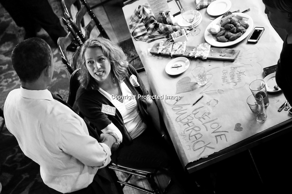 U.S. President Barack Obama greets a supporter, who drew her feelings on her table at the Common Man restaurant in Merrimack, New Hampshire, October 27, 2012.