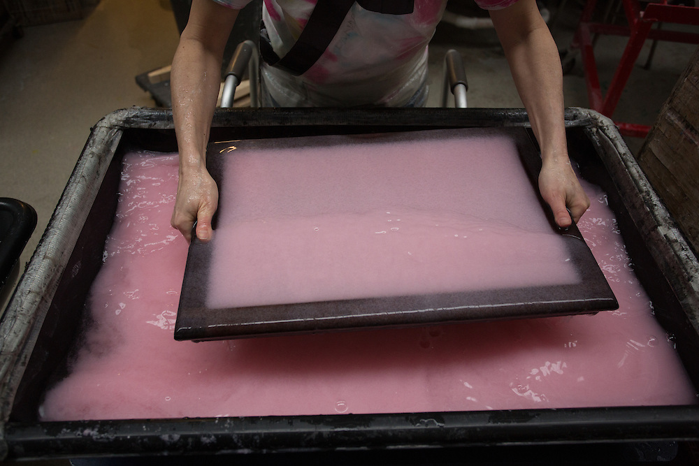 Mould and deckle are pulled from the vat to form the base layer of the sheet.