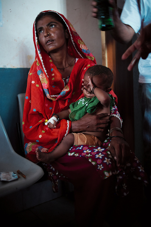 Rani Muhammad Alam with child Nadeem in the Bautoro District Hospital, Thatta, Sindh, Pakistan on July 1, 2011. Nadeem is 12 months old and malnourished and severely dehydrated.