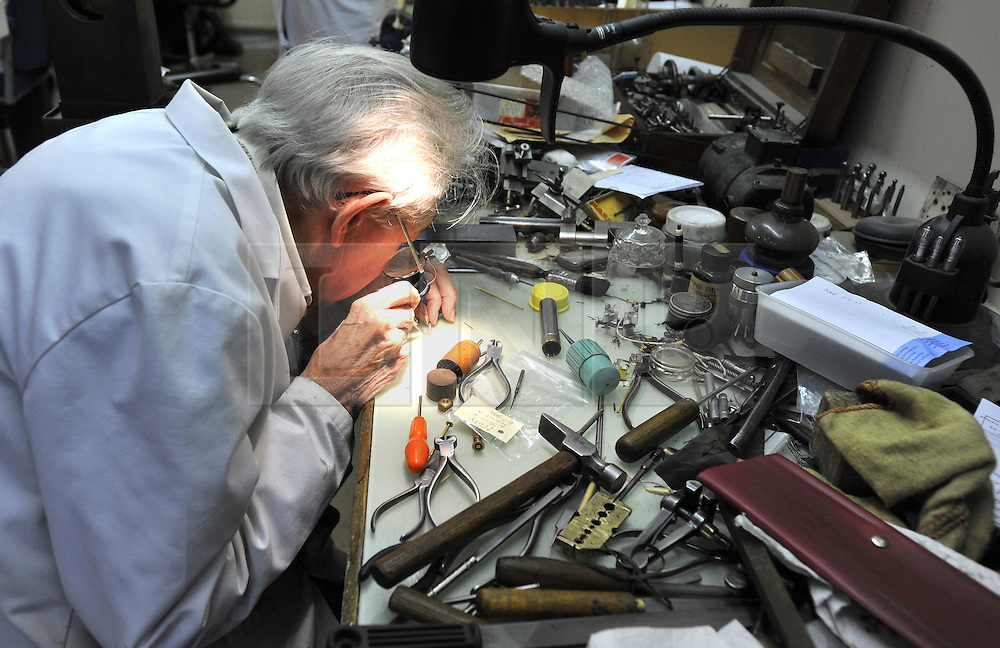"©London News pictures...28/10/2010.  Dudley Taylor, 76, a clockmaker all his life, working at his desk. Staff at Horological Workshops start the task of changing the 100's of clocks at their store in Guildford, Surrey, UK. Micahel Tooke who has owned the store for 43 years and worked in the clock business all his life said. ""at this time of year we get alot of people who bring clocks in for repair after they have changed the time incorreectly by winding back the hands manually"""