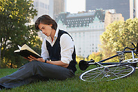 Man sitting on lawn reading book