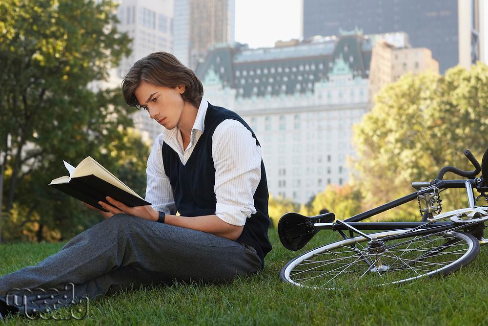 Man sitting on lawn reading book